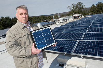 William Bickley, Sustainability Coordinator, poses with the solar panel array on top of Wilson Hall as he holds a sample section of one of the panels in his hands.