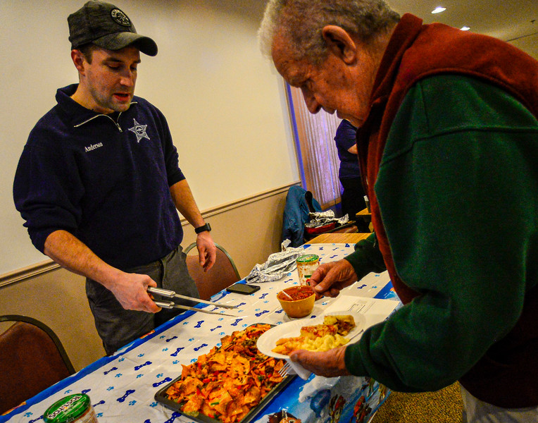 KRISTOPHER RADDER — BRATTLEBORO REFORMER<br /> Windham County Sheriff Mark Anderson serves up his nacho creation to Curly Worden during the Can Cops Cook event at the VFW, in Brattleboro, on Saturday, Feb. 29, 2020.
