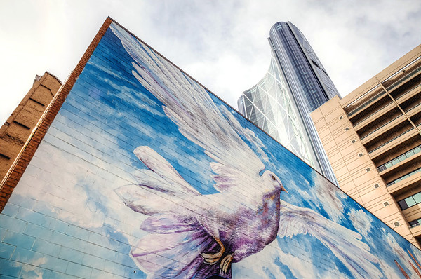 Mural on the Calgary Urban Project Society building with a view of The Bow skyscraper