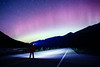 Jasper, Icefields Centre - Man in road with aurora and mountains