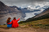 Banff, Icefields - Couple sitting and looking at Saskatchewan Glacier with him pointing at something in distance
