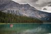 Yoho, Emerald Lake - Two people in a canoe beneath a distant ridge