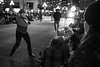 Vancouver Island, Victoria - Woman holding mobile phone taking picture of Newsies dance troupe in Christmas parade, black and white