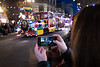Vancouver Island, Victoria - Woman holding mobile phone taking picture of train float in Christmas parade