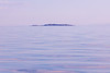 Campbell River, Water - Small distant island on the horizon with calm seas