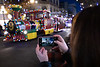 Vancouver Island, Victoria - Woman holding mobile phone taking picture of train float in Christmas parade, larger