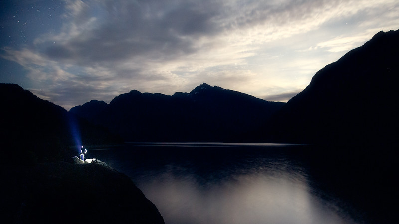 Campbell River, Buttle Lake - Man on cliff above lake under moonlit skies