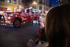 Vancouver Island, Victoria - Woman holding mobile phone taking picture of fire truck in Christmas parade