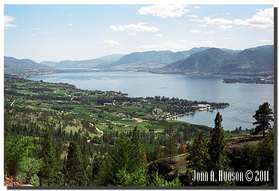 1664_1995011-R4-C4-NCS-BritishColumbia.jpg : Naramata, Okanagan Lake and Penticton [and Skaha Lake] in the far distance taken from the Kettle Valley rail bed walking trail north of Naramata.