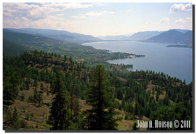 1595_1990008-R7-C4-NCS-BritishColumbia.jpg : Southern extremity of Okanagan Lake, looking south from the Kettle Valley rail bed north of Naramata. Naramata in the middle distance and Penticton [and Skaha Lake] in the far distance.