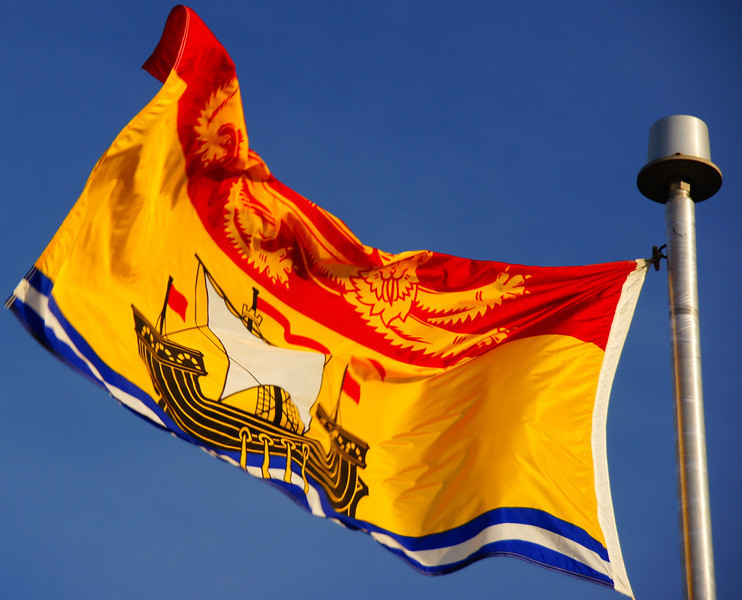 The New Brunswick provincial flag with lion & galleon flapping in the wind on a brisk fall afternoon in Fredericton, New Brunswick, Canada.