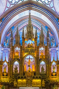 "The Notre-Dame Basilica is located in the historic district of Old Montreal, Quebec.  It is located next to the Saint-Sulpice Seminary and faces the Place d'Armes square.  The basilica was designed by James O'Donnell, an Irish-American Anglican from New York City, a proponent of the Gothic Revival architectural movement.   The main construction work took place between 1824 and 1829. The cornerstone was laid at Place d""Armes on September 1, 1824. The sanctuary was finished in 1830, and the first tower in 1841, the second in 1843. On its completion, the church was the largest in North America. It remained the largest in North America for over fifty years.  The vaults are colored deep blue and decorated with golden stars, and the rest of the sanctuary is decorated in blues, azures, reds, purples, silver, and gold. It is filled with hundreds of intricate wooden carvings and several religious statues. Unusual for a church, the stained glass windows along the walls of the sanctuary do not depict biblical scenes, but rather scenes from the religious history of Montreal. In 1886 Casavant Frères began building a new 32-foot pipe organ with 7000 individual pipes, four keyboards, 92 stops using electro-pneumatic action at the church, completing it in 1891.  Because of the splendor and grand scale of the church, a more intimate chapel, Chapelle du Sacré-Cœur (Chapel of the Sacred Heart), was built behind it, along with some offices and a sacristy. It was completed in 1888."
