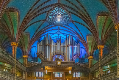 """The Notre-Dame Basilica is located in the historic district of Old Montreal, Quebec.  It is located next to the Saint-Sulpice Seminary and faces the Place d'Armes square.  The basilica was designed by James O'Donnell, an Irish-American Anglican from New York City, a proponent of the Gothic Revival architectural movement.   The main construction work took place between 1824 and 1829. The cornerstone was laid at Place d""""Armes on September 1, 1824. The sanctuary was finished in 1830, and the first tower in 1841, the second in 1843. On its completion, the church was the largest in North America. It remained the largest in North America for over fifty years.  The vaults are colored deep blue and decorated with golden stars, and the rest of the sanctuary is decorated in blues, azures, reds, purples, silver, and gold. It is filled with hundreds of intricate wooden carvings and several religious statues. Unusual for a church, the stained glass windows along the walls of the sanctuary do not depict biblical scenes, but rather scenes from the religious history of Montreal. In 1886 Casavant Frères began building a new 32-foot pipe organ with 7000 individual pipes, four keyboards, 92 stops using electro-pneumatic action at the church, completing it in 1891.  Because of the splendor and grand scale of the church, a more intimate chapel, Chapelle du Sacré-Cœur (Chapel of the Sacred Heart), was built behind it, along with some offices and a sacristy. It was completed in 1888."""