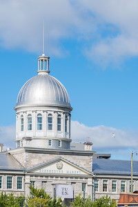 Bonsecours Market is a two-story domed public market. For more than 100 years, it was the main public market in the Montreal area. It also briefly accommodated the Parliament of United Canada for one session in 1849. Named for the adjacent Notre-Dame-de-Bon-Secours Chapel, it opened in 1847.  Closed in 1963 as a farmer's central market, it was slated for demolition. Today, the market is multi purpose facility with an up-scale mall that houses outdoor cafés, restaurants and boutiques.  Bonsecours Market was designated a National Historic Site of Canada in 1984.
