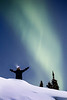 Yellowknife, Vee Lake - Man with arms up in the snow under aurora