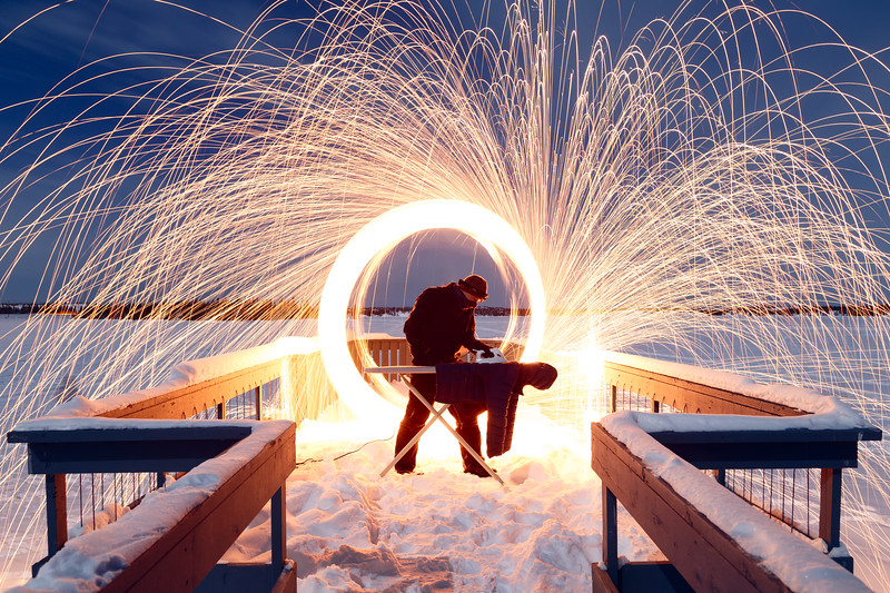 Yellowknife, Long Lake - Man ironing in the snow at night with burning steel wool