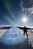 Yellowknife, Vee Lake - Man standing next to igloo under aurora