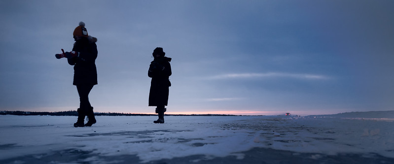 Yellowknife, Dettah Ice Road - Two women walking along the ice road away from a vehicle