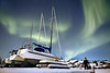 Yellowknife, Giant Mine - Man standing next to boats under the aurora