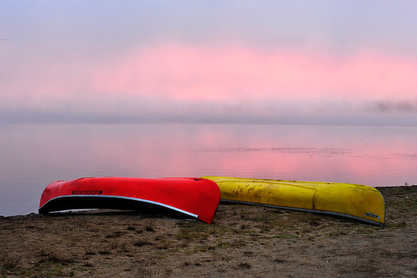 Canoes on shore with pink sunrise