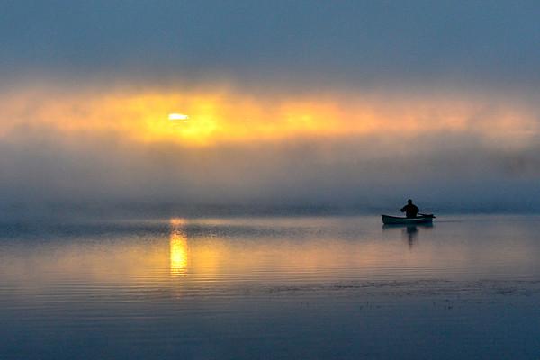 Canoeist thru the sunrise