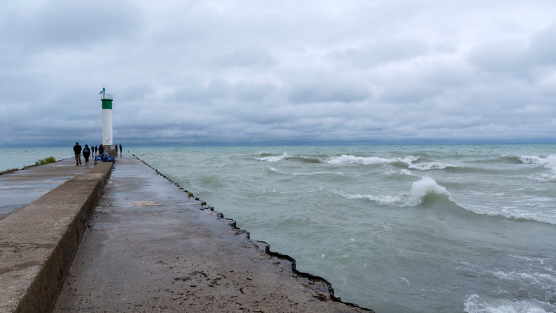 Grand Bend lighthouse at the end of the pier during a stormy day with many crashing waves.
