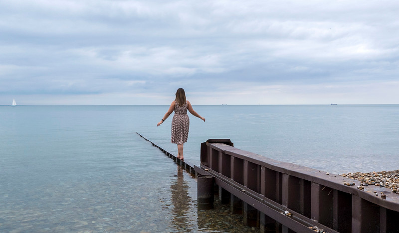 Balancing on a beam out to the crystal clear waters of Canatara Beach. Blue flag beach in Sarnia, Ontario, Canada.