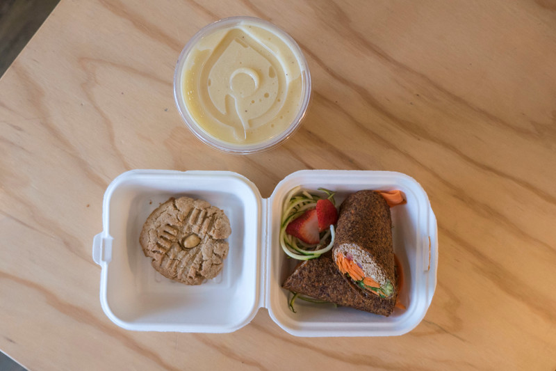 Food from Greens Organic Cafe in Sarnia, Ontario. Pina colada smoothie, walnut taco wrap, peanut butter cookie. Vegan.