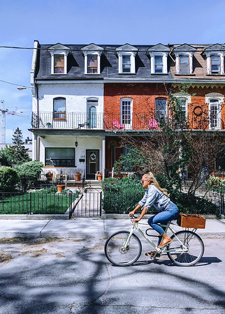 Woman biking in a street by Trinity Bellwoods Park in the city of Toronto, Ontario, Canada.