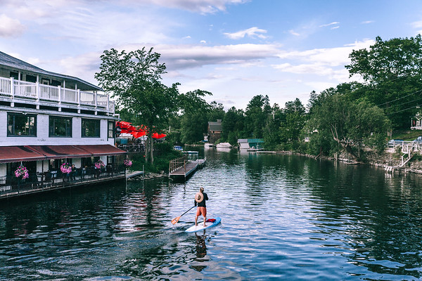 A man on a paddleboard on the river adjacent to Lake Massawippi in the charming village of North Hatley which is known as one of the most beautiful villages in Quebec, Canada.