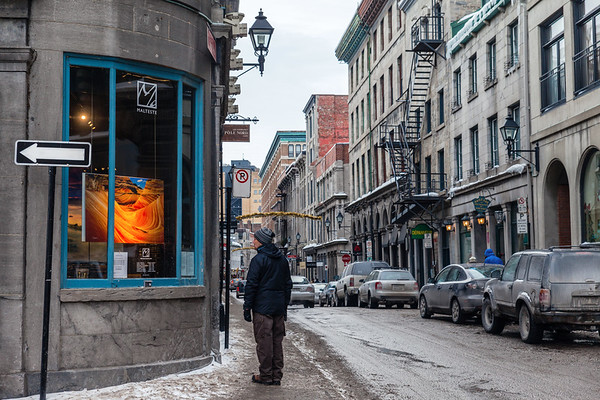 Man looking at the window of an art gallery in Old Montreal, Quebec, Canada.