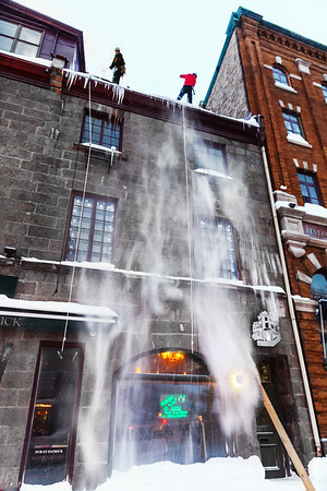 Worker removing snow from a roof in Old Quebec City