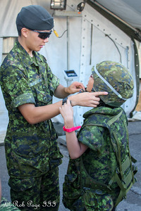 Putting a military rucksack on a boy - Toronto, ON ... September 1, 2012 ... Photo by Rob Page III