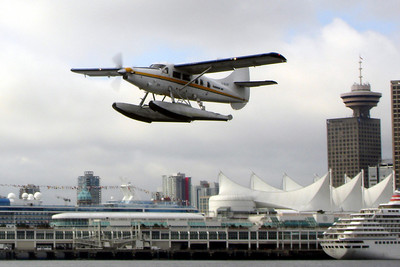 A seaplane takes off with cruise boats and skyscrapers in the background - Vancouver, BC ... June 25, 2007 ... Photo by Rob Page III