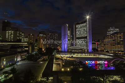 Toronto Canada City Hall at night and surrounding Toronto downtown buildings.