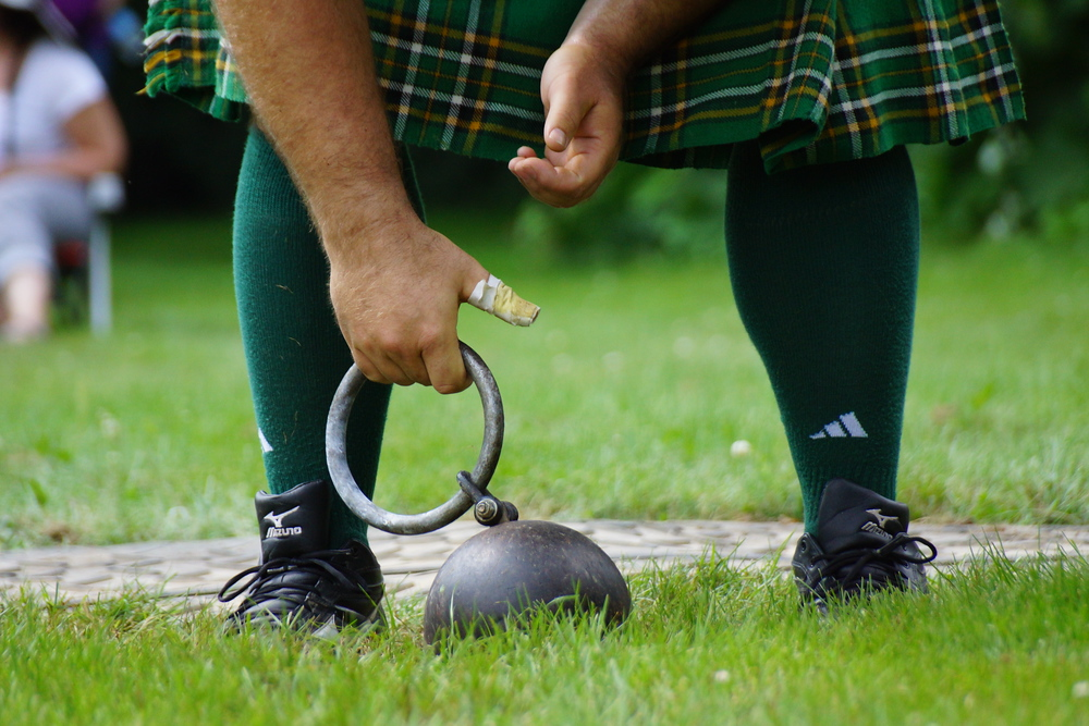 A close up shot of man bending down to pick up the handle of the weight toss at the New Brunswick Highland Games