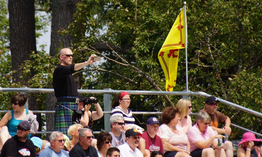 A spectator wearing a kilt snaps a photo at the Highland Games in Fredericton, New Brunswick