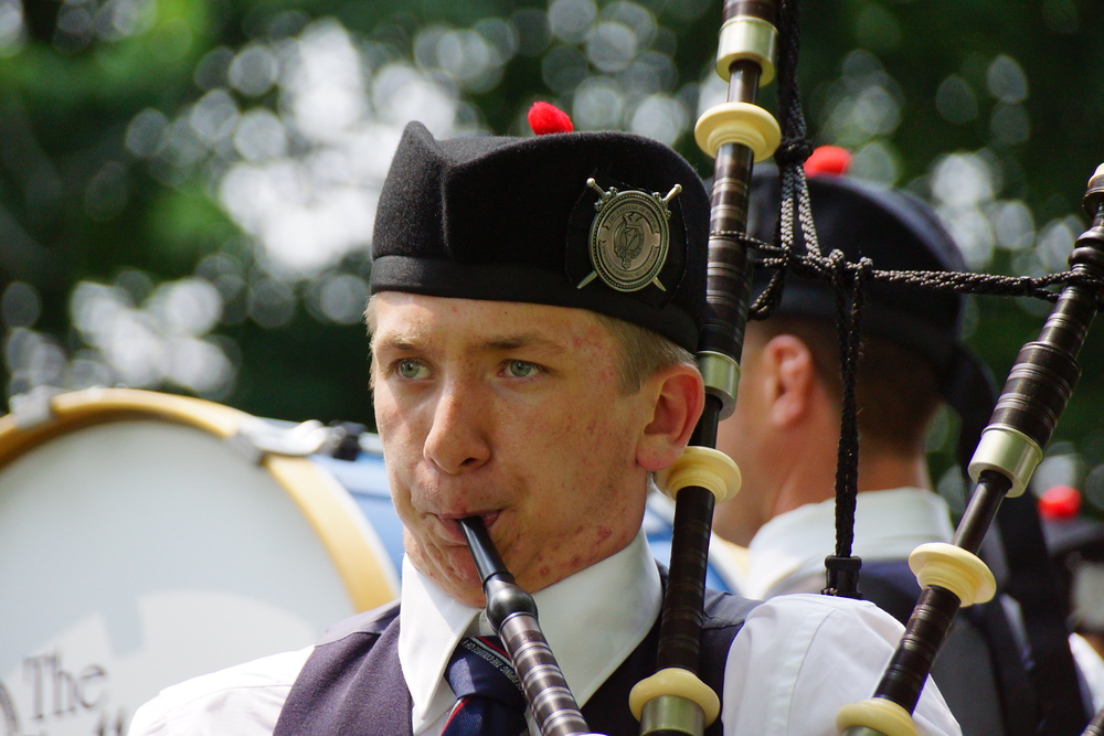 A close up shot of the face of a man blowing into the bagpipes at the New Brunswick Highland Games held in Fredericton, Canada.