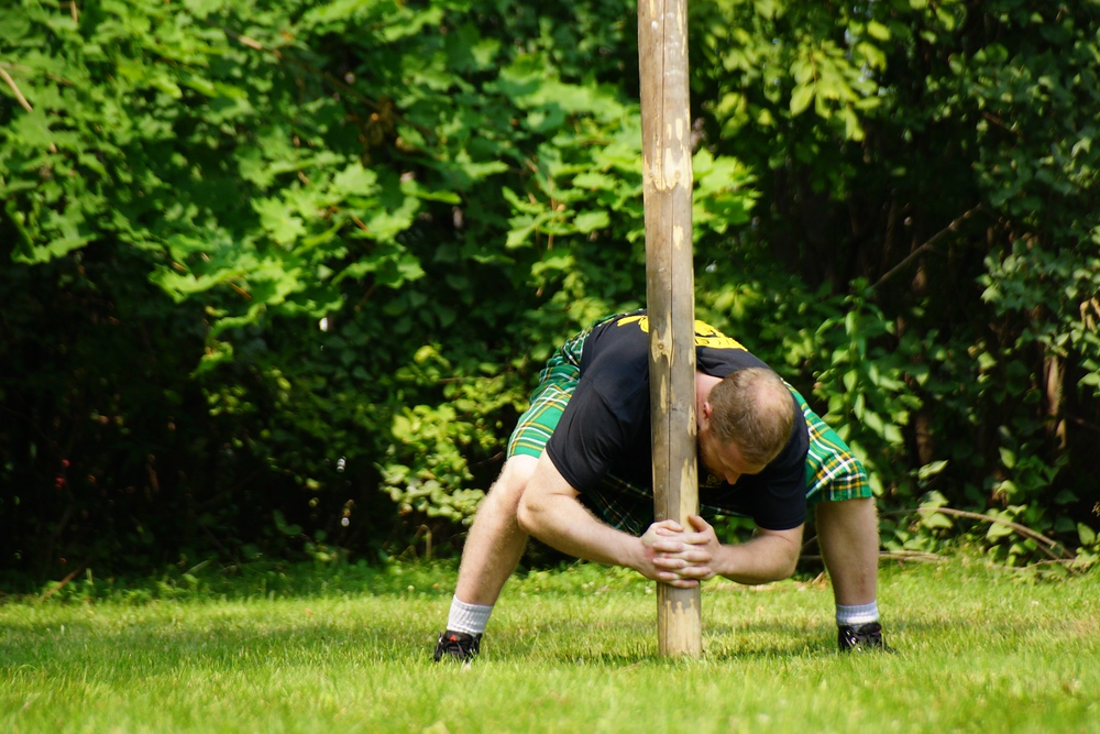 A young man is crouching down to life the caber to an upright position before tossing it at the Highland Games