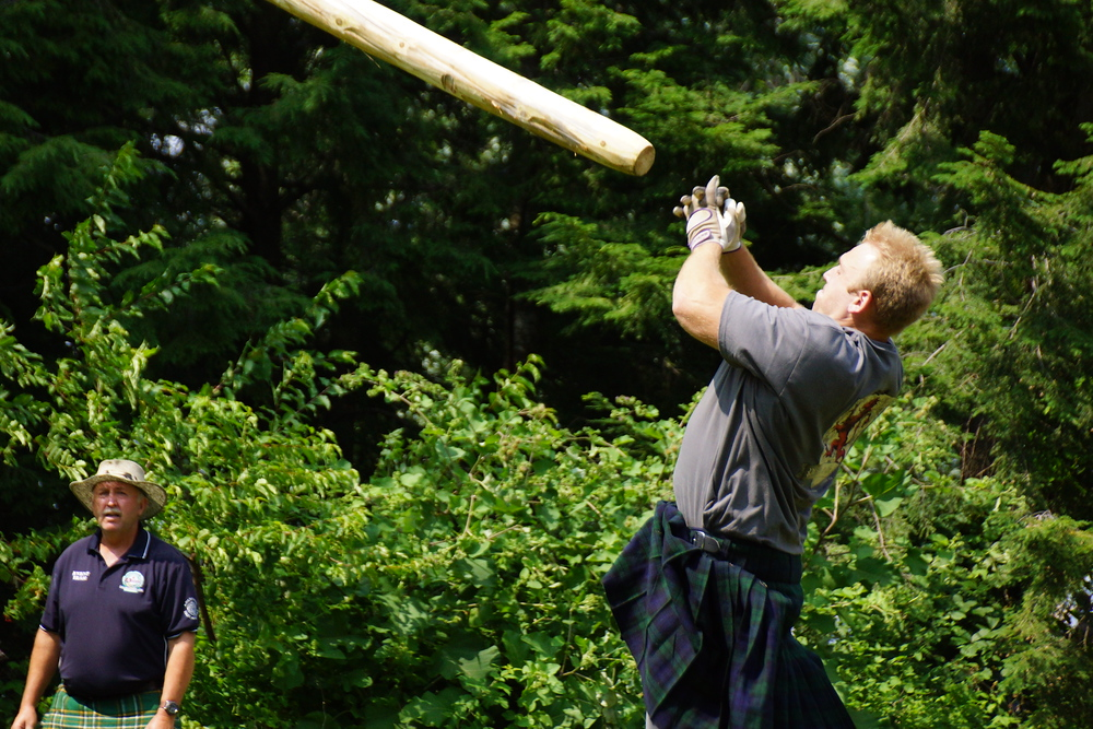 A man launching a caber into the air at the New Brunswick Highland Games in Fredericton, Canada