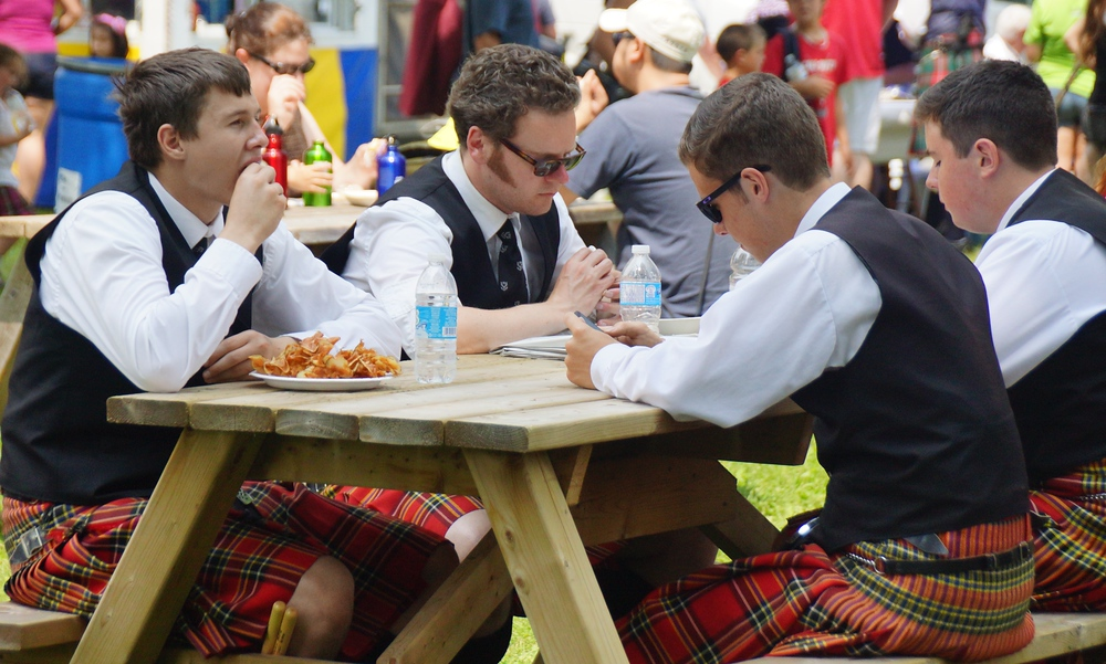 A group of kilted young men and teenagers sit down on a picnic bench to enjoy some snack food at the New Brunswick Highland Games