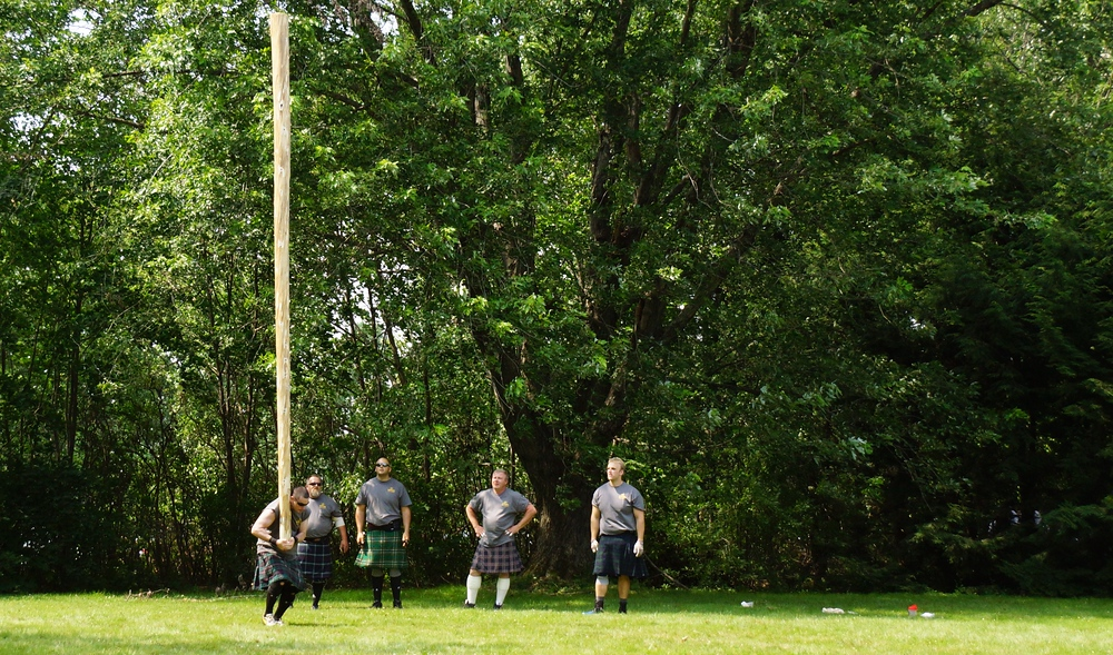 A man lifting a caber vertically before throwing it at the Highland Games in New Brunswick