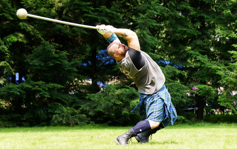 A man wielding an Ancient hammer swings it with maximum velocity over his head at the Highland Games
