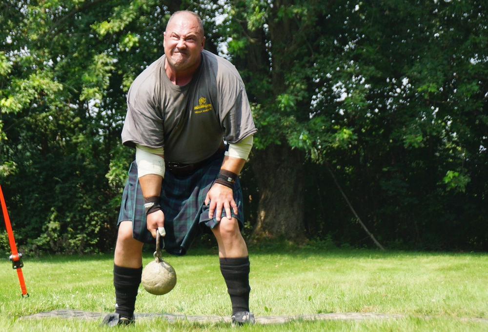 A man with a distinct facial expression of physical strain as he tries to toss a heavy weight over his head.