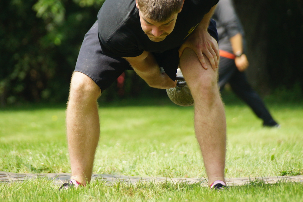 A young man crouches down swinging a weight below his legs prior to releasing it in the air at the Highland Games in Fredericton
