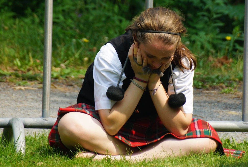 A girl sits down to take a break while resting her hands on her face at the New Brunswick Highland Games