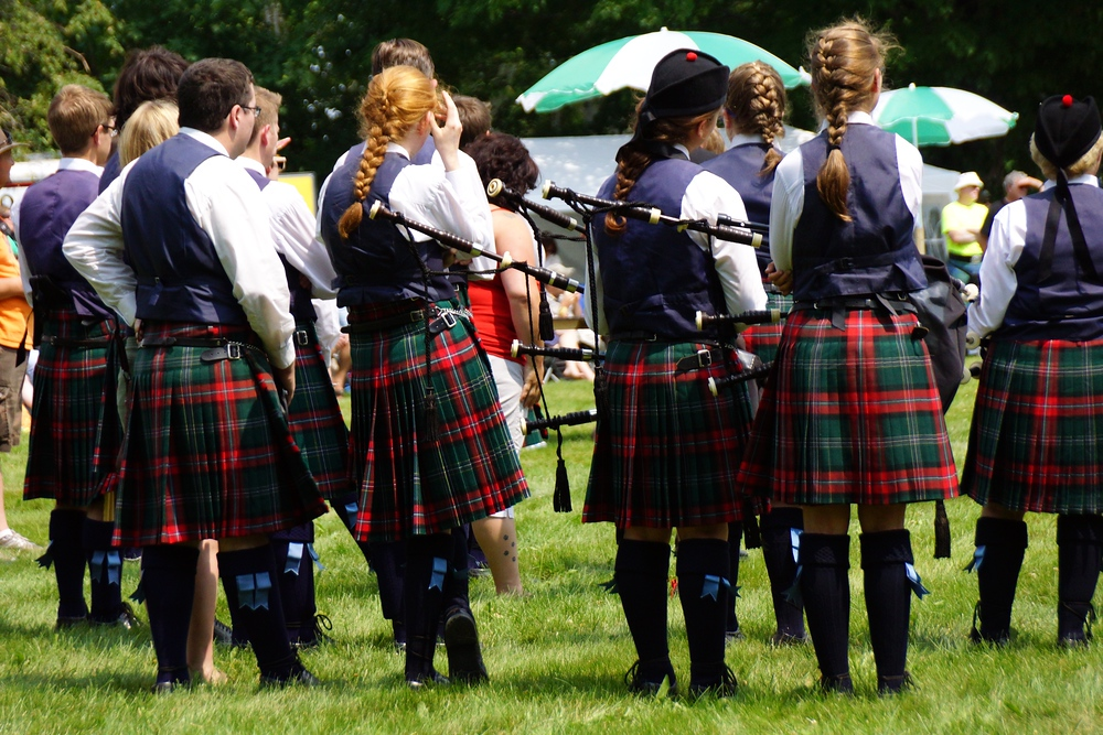 A piping and drumming band taking a rest on the field at the Fredericton Highland Games in New Brunswick, Canada