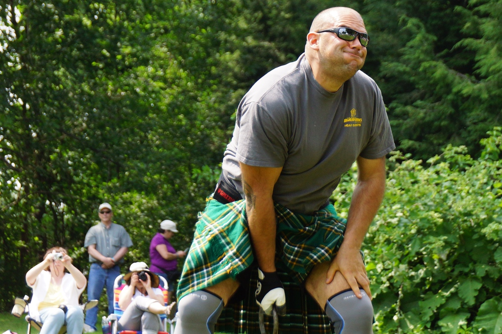 The facial expression of a man mustering up strength to throw a weight over his head at the New Brunswick Highland Games