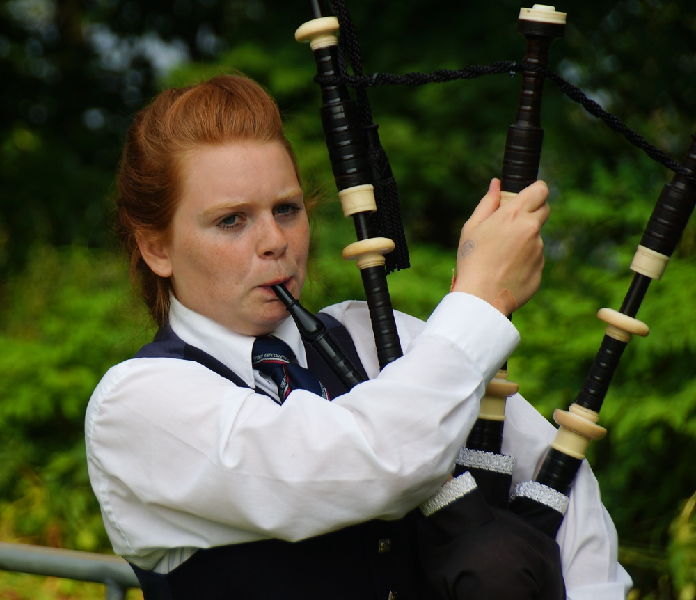 A young red headed lady warming up by playing the bagpipes before the competition started at the Highland Games