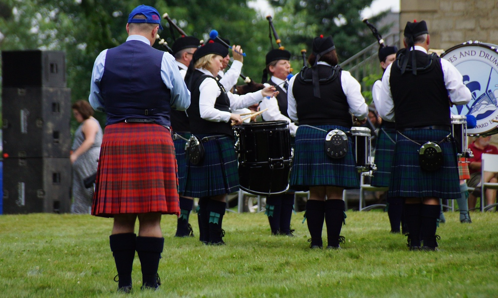 A lone man wearing a red kilt stands behind a band wearing different style kilts at the New Brunswick Highland Games